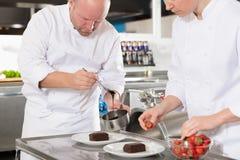 Los cocineros profesionales adornan la torta del postre con la hoja del limón Imagenes de archivo