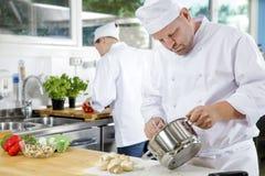 Los cocineros profesionales hacen platos de la comida en cocina grande Imagen de archivo libre de regalías