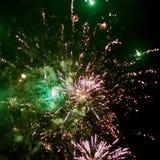 Los cohetes de los fuegos artificiales estallan en cielo nocturno con las porciones de humo y de chispas fotos de archivo libres de regalías