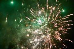 Los cohetes de los fuegos artificiales estallan en el cielo nocturno iluminado verde imágenes de archivo libres de regalías