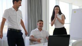 Los colaboradores alegres con el ordenador en la tabla aplauden en el trabajo en espacio de oficina metrajes