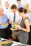 Los colegas del asunto comen los aperitivos de la comida fría