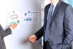 Los colegas del negocio que trabajan y que analizan figuras financieras Imágenes de archivo libres de regalías