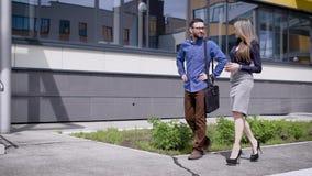 Los colegas en trabajo dan un paseo cerca del edificio de la forma en su hora de la almuerzo, ellos van hacia la oficina a contin almacen de metraje de vídeo