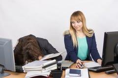Los colegas femeninos en la oficina, una tenían dormido caido en una pila de carpetas, y los segundos la miraban Fotografía de archivo