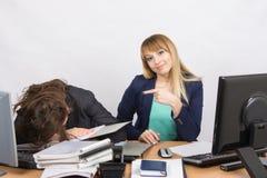 Los colegas femeninos en la oficina, una tenían dormido caido en una pila de carpetas, y los segundos muestran su finger y la mir Imagenes de archivo