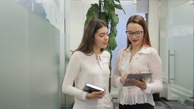 Los colegas femeninos están hablando mientras que se colocan en oficina moderna metrajes