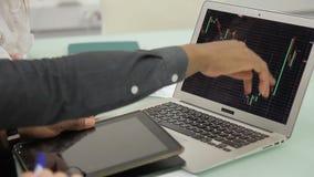 Los colegas jovenes comunican, usando el ordenador portátil y la tableta en oficina moderna metrajes