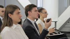 Los colegas jovenes están en la reunión oficial en oficina moderna dentro almacen de video