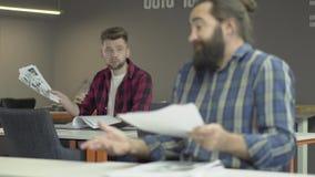 Los colegas leyeron los papeles con planes de trabajo Un oficinista u hombre de negocios está indignado en el mún pokachateley y  metrajes