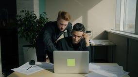 Los colegas masculinos están hablando con el ordenador portátil en la tabla en oficina moderna almacen de metraje de vídeo