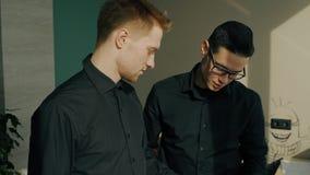 Los colegas masculinos jovenes están hablando la colocación en oficina moderna metrajes