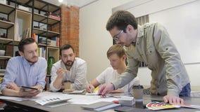 Los colegas masculinos trabajan en la oficina, discutiendo el modelo del diseño en oficina almacen de video