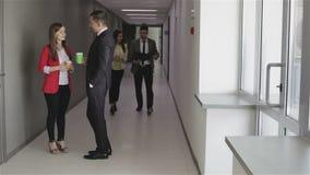 Los colegas mujer y hombre están hablando en vestíbulo de la oficina almacen de video