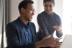 Los colegas multi?tnicos sonrientes discuten problemas del trabajo en oficina fotografía de archivo