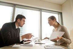 Los colegas que discuten en el lugar de trabajo, discrepan sobre el documento, error imagen de archivo