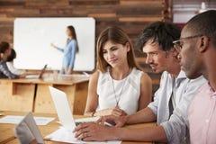 Los colegas trabajan juntos en el ordenador portátil en una oficina ocupada imagen de archivo