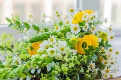 Los colores amarillos y verdes de la primavera florecen en un bouqet Imagenes de archivo