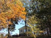Los colores de la caída rodean la pequeña casa amarilla de la granja Imagen de archivo