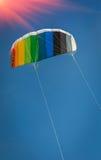 Los colores del arco iris de la cometa vuelan arriba en el cielo Fotografía de archivo