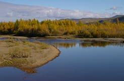 Los colores del otoño rodean un lago y nubes grises arriba Fotografía de archivo