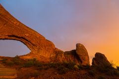 Los colores dramáticos, las nubes y la lluvia de la puesta del sol en parque nacional de los arcos abandonan Fotografía de archivo
