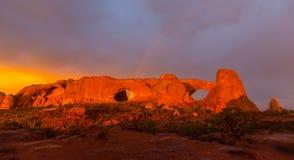 Los colores dramáticos, las nubes y la lluvia de la puesta del sol en parque nacional de los arcos abandonan Imágenes de archivo libres de regalías