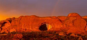Los colores dramáticos, las nubes y la lluvia de la puesta del sol en parque nacional de los arcos abandonan Fotos de archivo