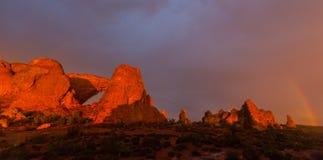 Los colores dramáticos, las nubes y la lluvia de la puesta del sol en parque nacional de los arcos abandonan Imagenes de archivo