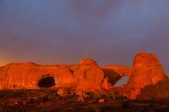Los colores dramáticos, las nubes y la lluvia de la puesta del sol en parque nacional de los arcos abandonan Fotografía de archivo libre de regalías