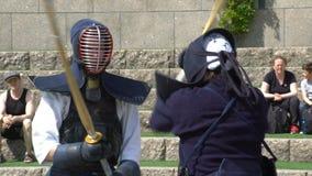 Los combatientes de Kendo practican el luchar con un shinai de bambú de la espada en un parque de la ciudad almacen de metraje de vídeo
