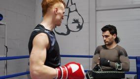 Los combatientes jovenes están discutiendo golpes durante práctica en ringside en el entrenamiento en gimnasio almacen de video
