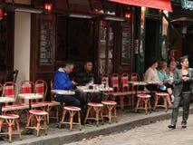 Los comensales disfrutan de un almuerzo en un bistro al aire libre Imagen de archivo libre de regalías