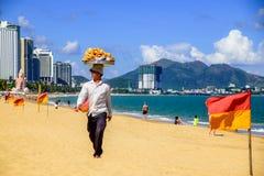 Los comerciantes venden la comida local a los turistas en una playa del mar y de las montañas Imágenes de archivo libres de regalías