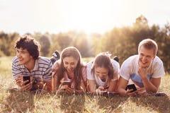 Los compañeros alegres sonríen mientras que dígase que las anécdotas, utilizan los teléfonos elegantes modernos, tienen picninc a Fotografía de archivo