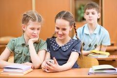 Los compañeros de clase juegan con el teléfono móvil en el pausa de las lecciones Imagenes de archivo