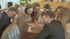 Los compañeros de clase se sientan alrededor del escritorio y discuten la tarea de la escuela con el ordenador portátil Escuela r metrajes