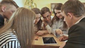 Los compañeros de clase se sientan alrededor del escritorio y discuten la tarea de la escuela con la tableta Escuela rusa metrajes