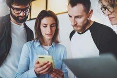 Los compañeros de trabajo combinan el trabajo con los dispositivos móviles en la oficina moderna Concepto de la reunión de negoci imagenes de archivo