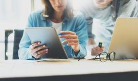 Los compañeros de trabajo combinan proceso de la reunión de reflexión en estudio del diseño moderno Tableta del informe de la lec Fotos de archivo