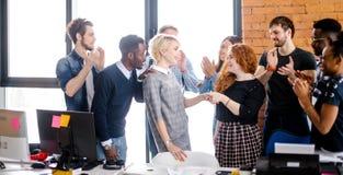 Los compañeros de trabajo están felicitando al nuevo empleado que ha hecho experiencia profesional imágenes de archivo libres de regalías
