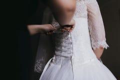 Los compinches, dama de honor ayudan a la novia que consigue lista para su DA que se casa Fotografía de archivo libre de regalías