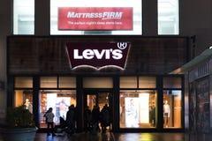 Los compradores caminan más allá de una tienda de ropa de la venta al por menor del ` s de Levi en New York City, Levi Strauss y  fotos de archivo