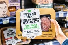Los compradores dan llevar a cabo un paquete de planta de la marca de la carne del más allá basaron las empanadas de la hamburgue imagen de archivo libre de regalías