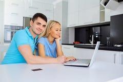 Los compradores de un par con una tarjeta de crédito hacen compras con un ordenador portátil Fotografía de archivo libre de regalías