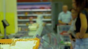 Los compradores eligen las ensaladas, empleados de la tienda embalan almacen de metraje de vídeo