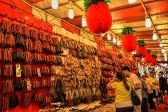 Los compradores negocian sobre las salchichas chinas en venta en Singapur Chinatown Imágenes de archivo libres de regalías