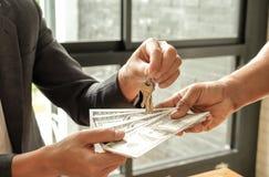 Los conceptos, los compradores y los vendedores del negocio casero dan el dinero del dólar, venta Imagen de archivo libre de regalías