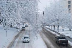 Los conductores navegan un camino nevado mientras que nievan Foto de archivo