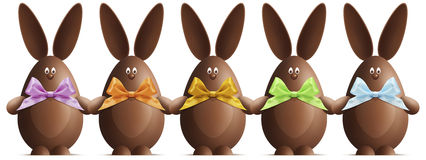 Los conejitos de pascua del chocolate con las cintas arquean en diversos colores encendido Foto de archivo libre de regalías